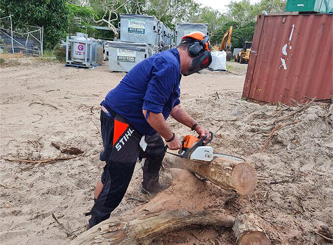 Man cutting a log wood with a chainsaw